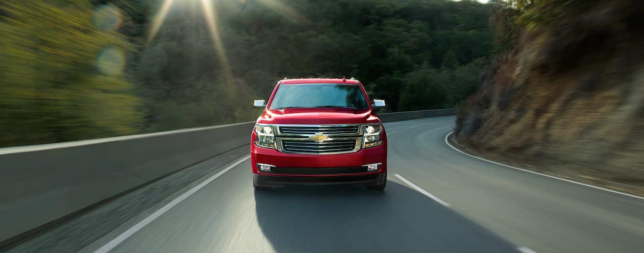 A red 2019 Chevy Tahoe racing down a winding road