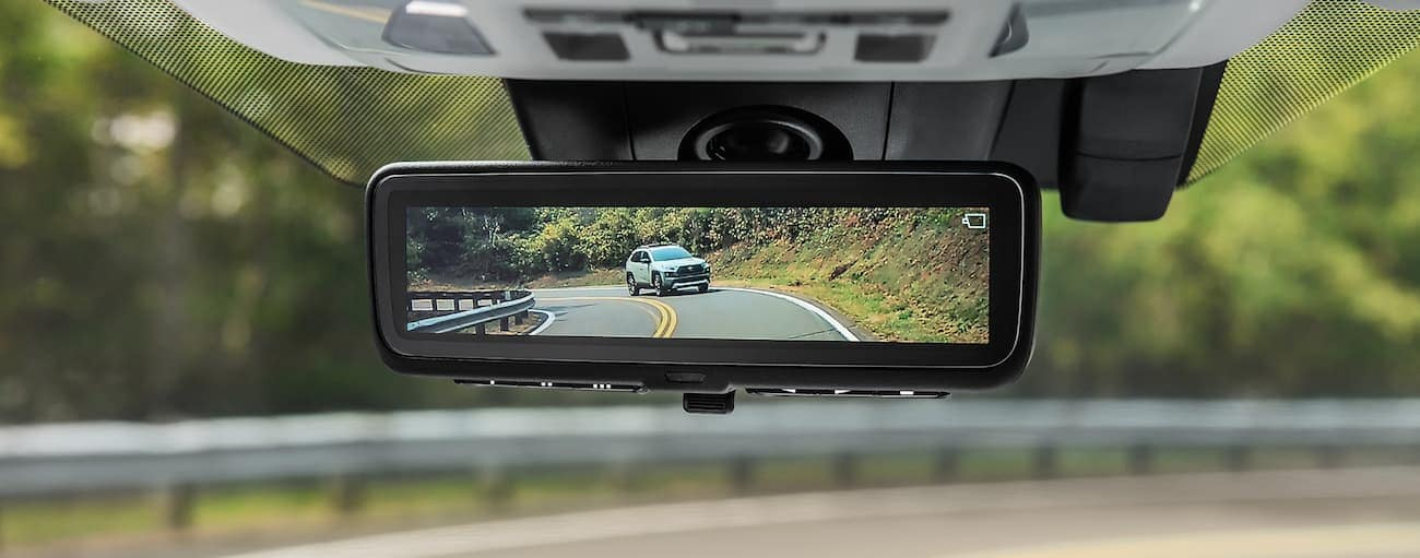 Looking at the rearview mirror which shows a rear camera with a 2019 Toyota RAV4 behind the driver