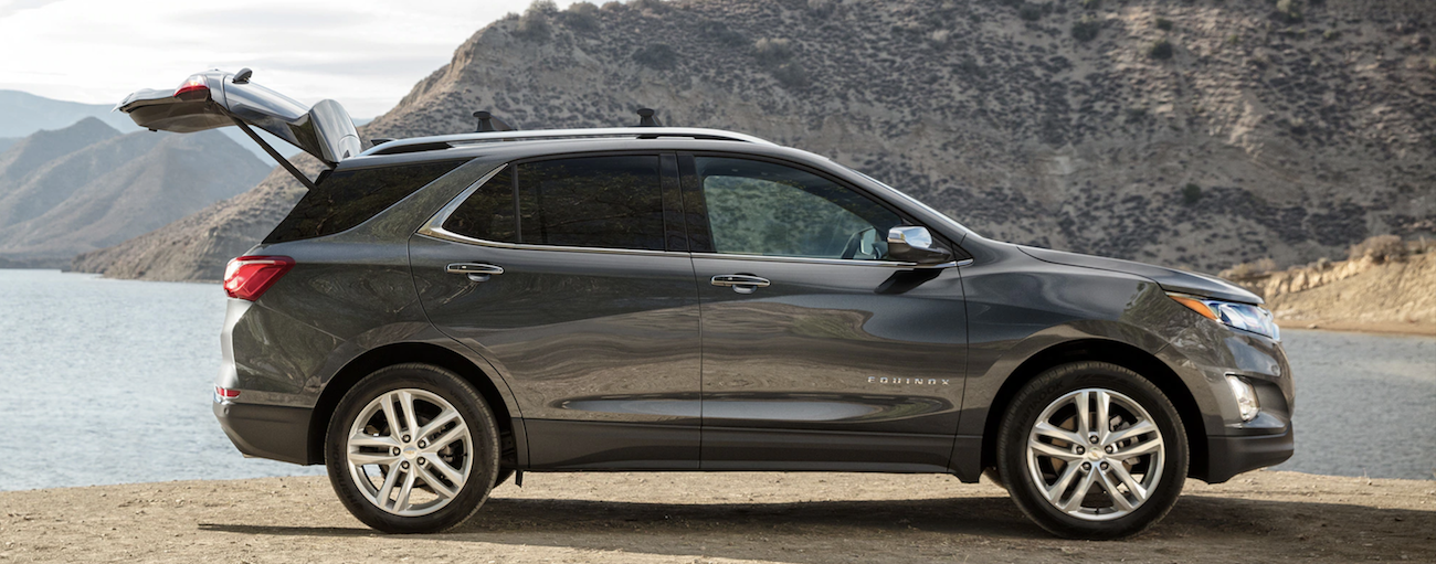 A dark gray 2019 Chevy Equinox at a lake with its rear hatch open