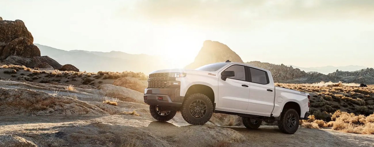 A white 23019 Chevy Silverado powers over huge desert rocks on a off-roading trim