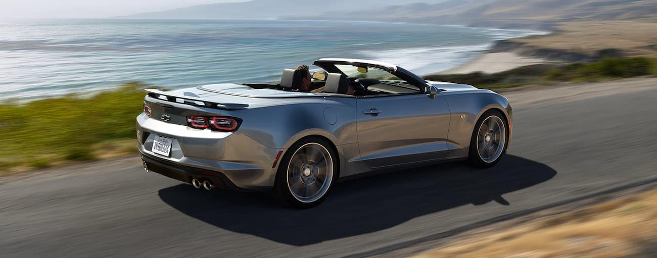 A silver 2019 Chevy Camaro convertible driving along a beach road