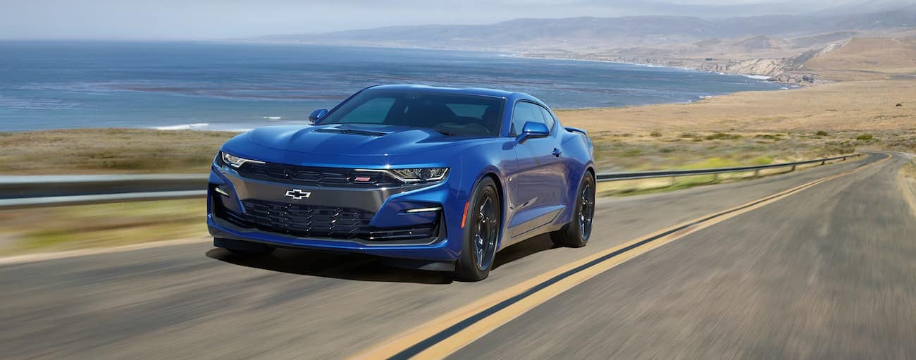 A blue 2019 Chevy Camaro drives by a body of water