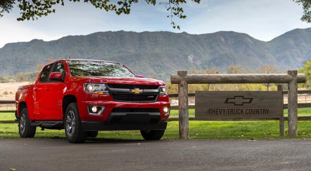 A red 2019 Chevy Colorado in front of a split rail fence that reads Chevy Truck Country