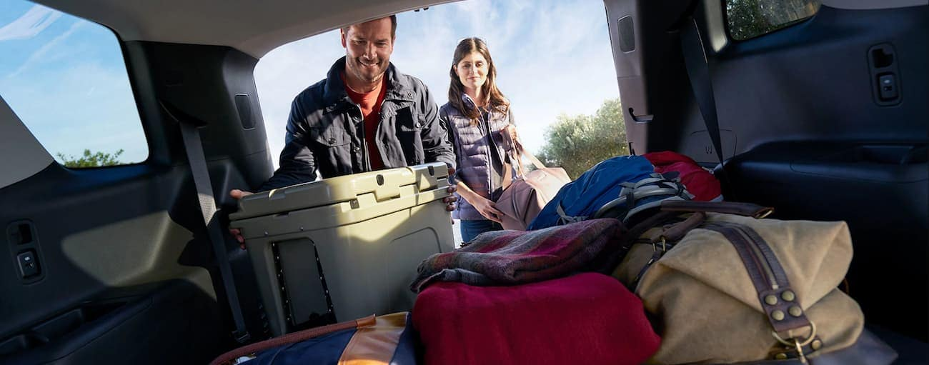 A man and woman load cargo into the back of a Traverse after winning 2019 Chevy Traverse vs 2019 Nissan Pathfinder