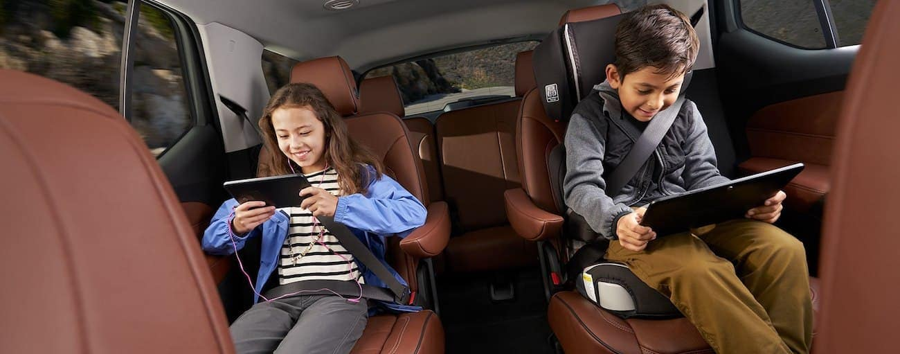 Two children play on their tablets in a Traverse happy that they won 2019 Chevy Traverse vs 2019 Nissan Pathfinder