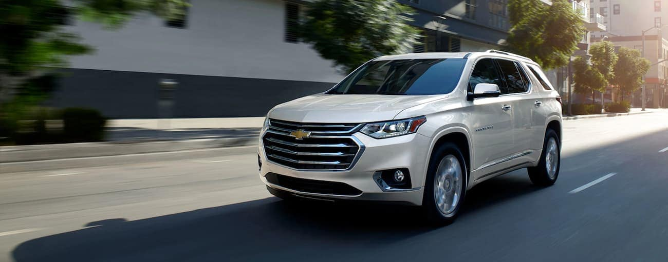 A white Traverse drives through a city, victorious after the battle of 2019 Chevy Traverse vs 2019 Nissan Pathfinder