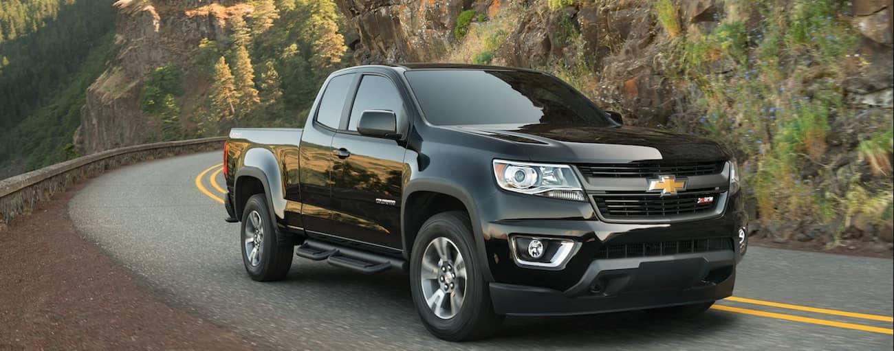 A black 2019 Chevy Colorado travels a tight mountain road