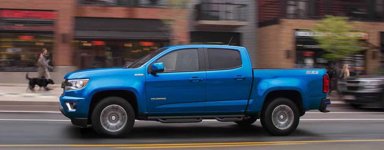 A blue 2019 Chevy Colorado cruises a busy city street