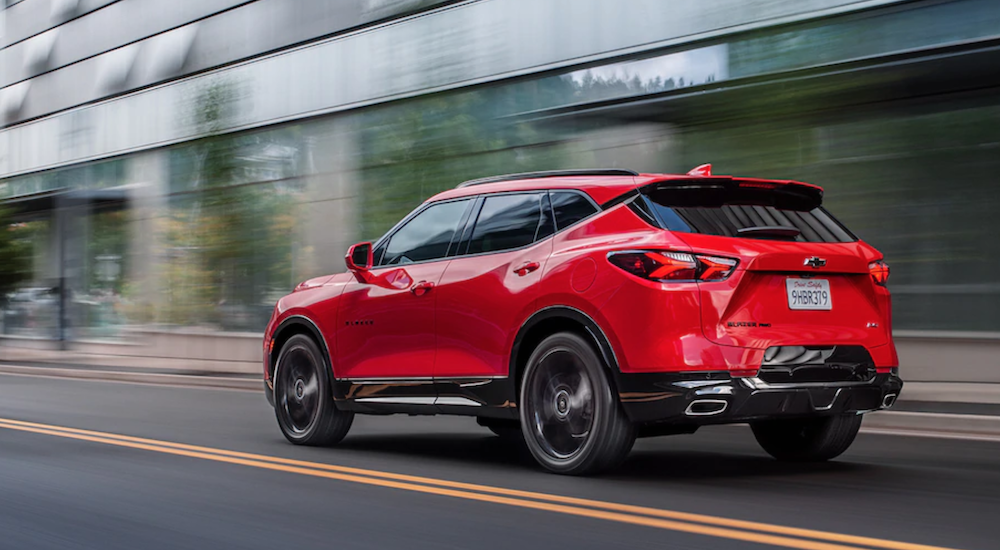 A red 2019 Chevy Blazer RS is driving away from view on a city street.