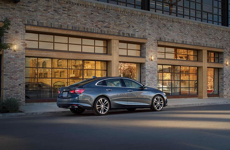 side profile of gray 2019 Chevy Malibu driving past modern building