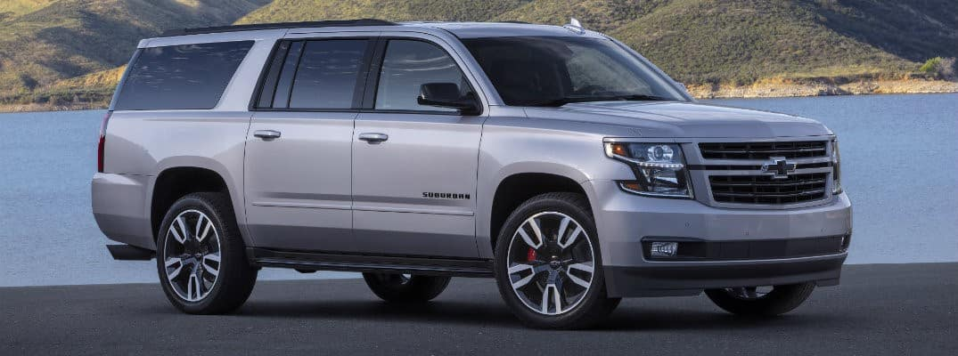 silver 2019 Chevy Suburban parked by water