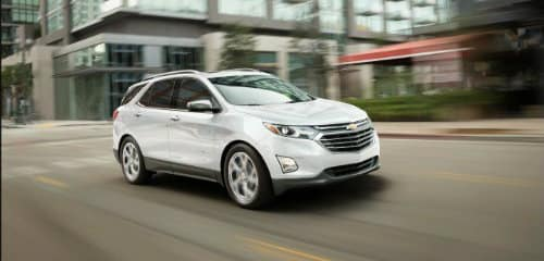 white 2019 Chevy Equinox driving through downtown