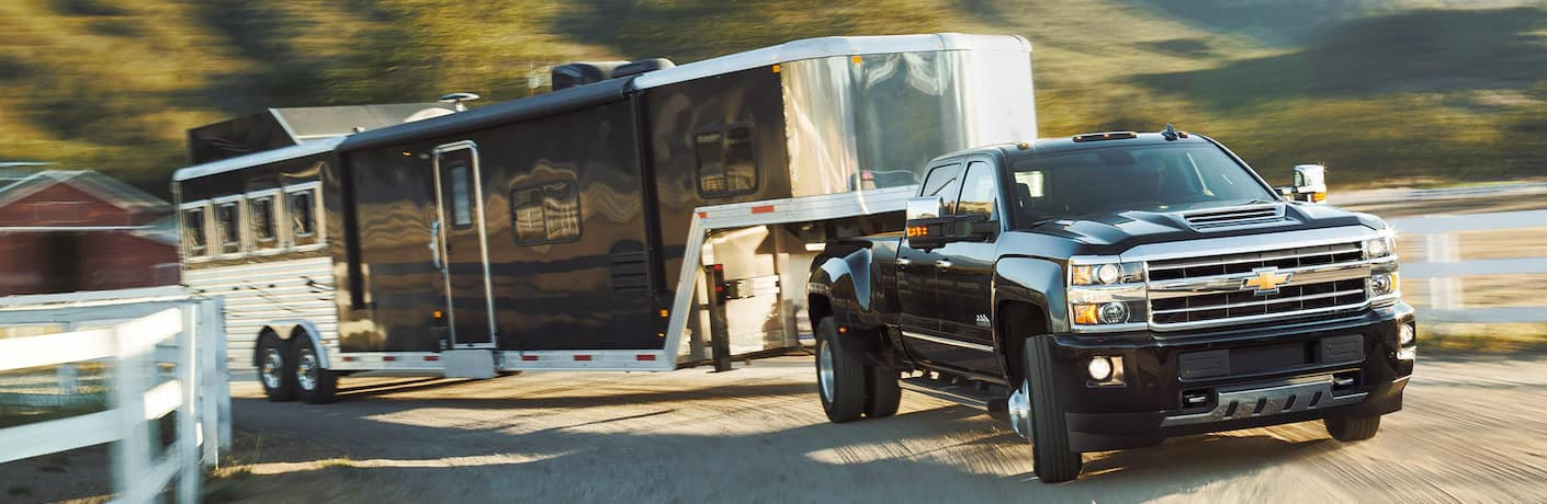 Black 2019 Chevrolet Silverado 3500HD towing a black and silver trailer