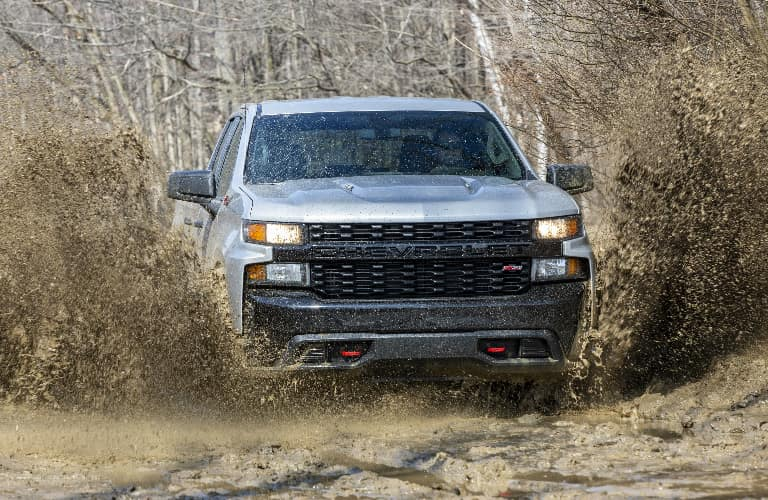 Silver 2020 Chevrolet Silverado 1500 driving on muddy terrain