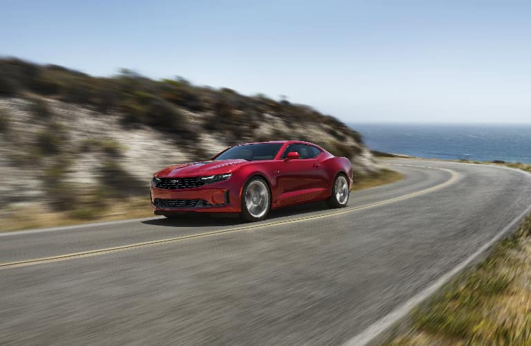 Red 2020 Chevrolet Camaro driving on a coastal road