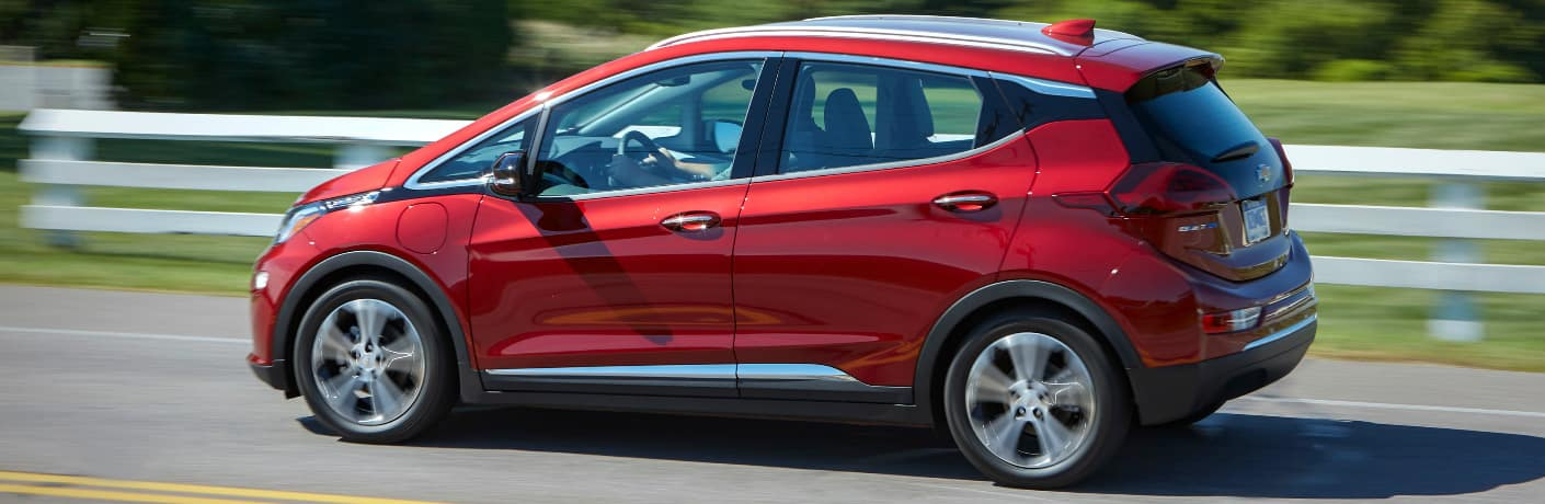 Red 2020 Chevrolet Bolt EV driving by white fence