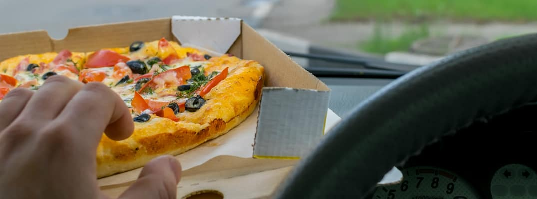 Driver grabbing a pizza from the dashboard of a car