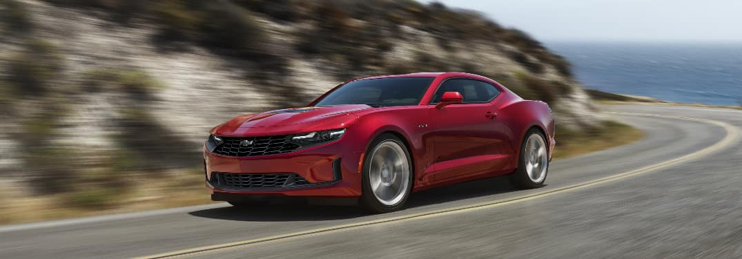 Red 2020 Chevrolet Camaro driving through a curve on a coastal road