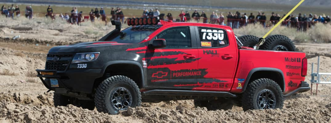 Side view of red and black Chevrolet Colorado ZR2 competing in a Best in the Desert Race