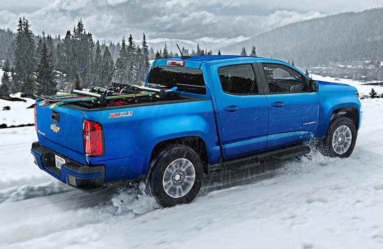 Blue 2020 Chevrolet Colorado driving on a snowy road