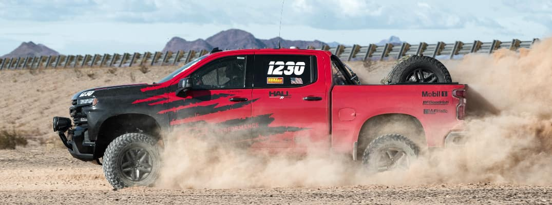 Side view of red and black 2020 Chevrolet Silverado off-road race truck