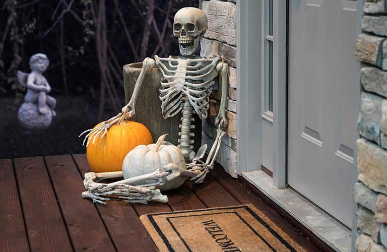 A skeleton sitting next to a door with two pumpkins