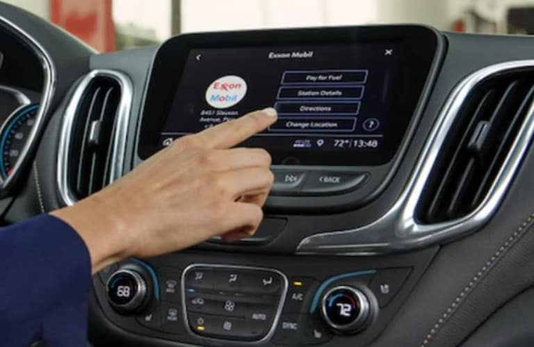 hand touching a screen in a Chevrolet vehicle