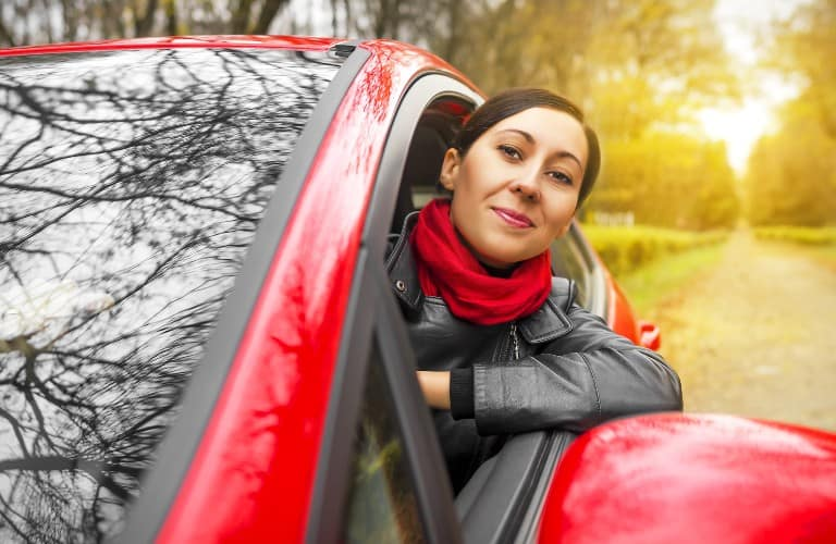 happy woman in a red car