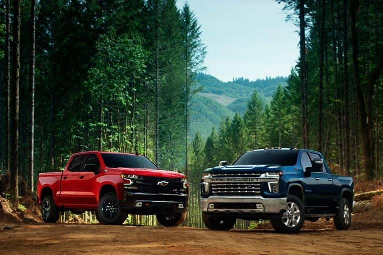 two 2021 Chevrolet Silverado trucks in a forest