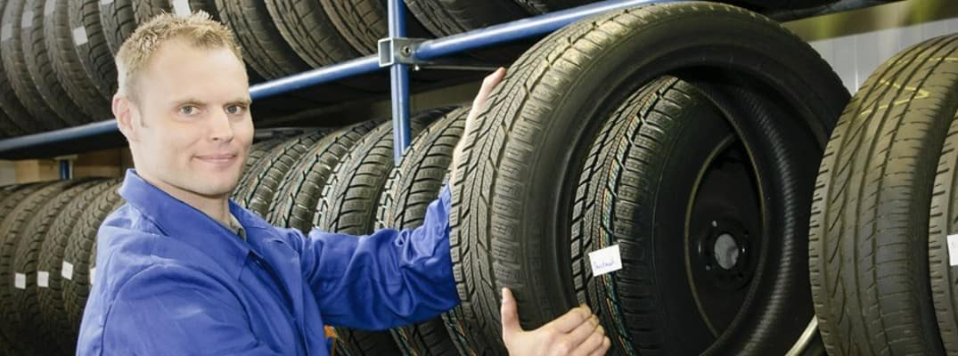 a man holding a tire by other tires