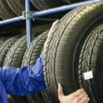 a man holding a tire by a rack of tires