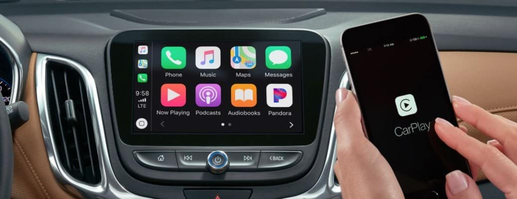 apps on a vehicle's display screen and a hand holding a phone