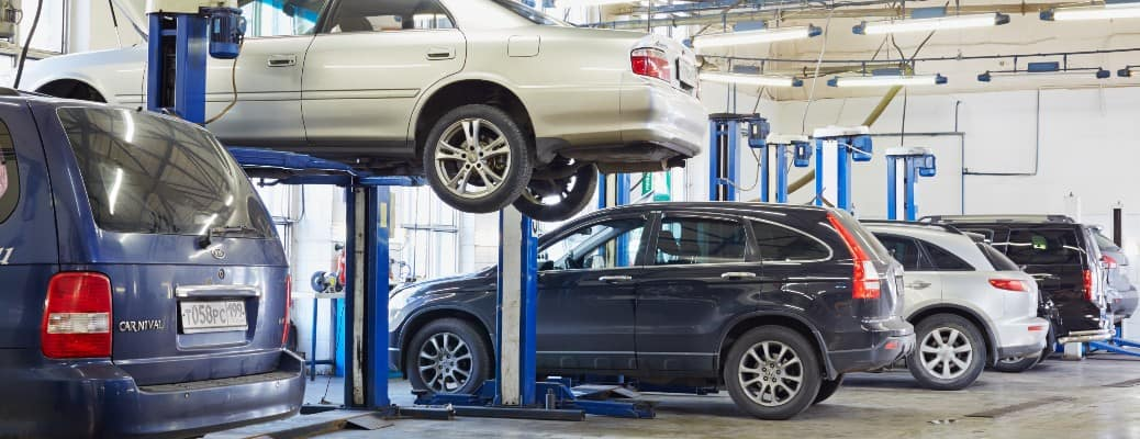 cars in a service center with one lifted up