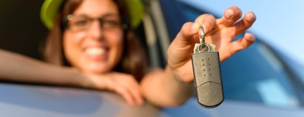 a woman holding a set of car keys