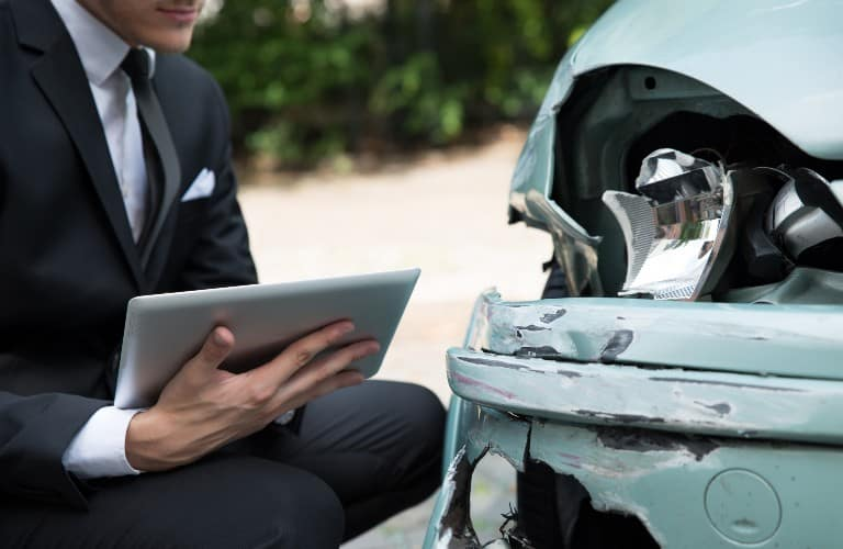 a torso with a laptop next to a vehicle
