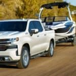 White 2021 Chevy Silverado Towing a Boat on the Coast