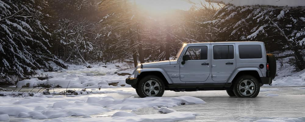 White Jeep Wrangler parked on icy terrain in a forest with the sun setting behind it