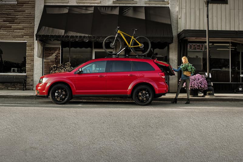 Woman loading the trunk of a red Dodge Journey parked on the street with a yellow bike on top of it