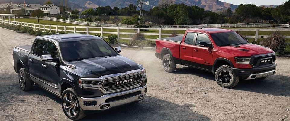 Two 2019 RAM 1500 trucks driving on country road