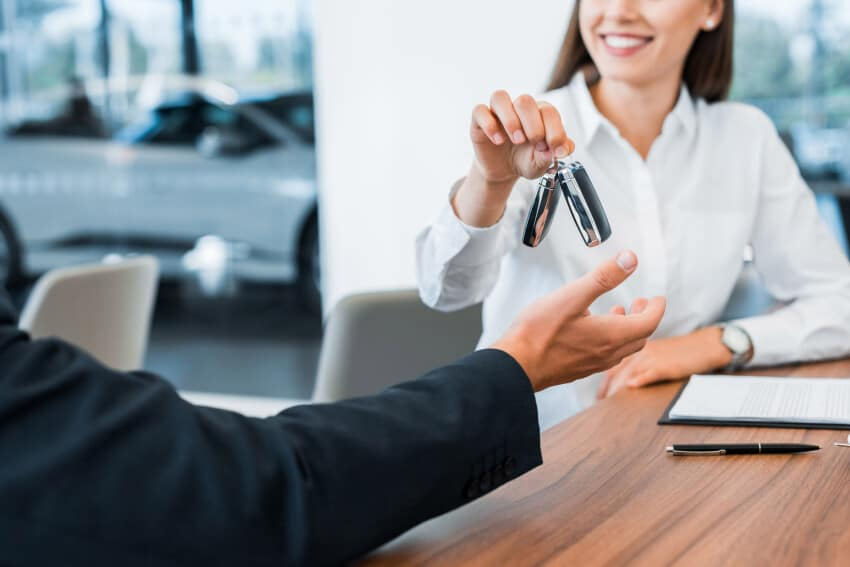 Car dealer giving car key to buyer