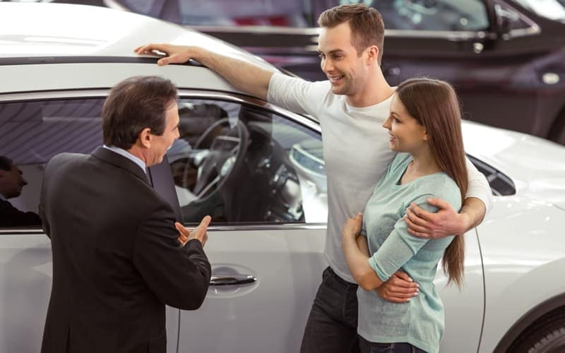 Car Salesman Speaking with Couple