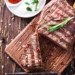 Steak, tomatoes, mushrooms, and sauce on wood table