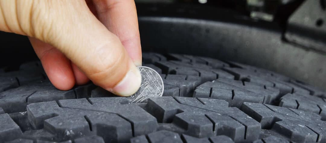 Person measuring tire depth with penny