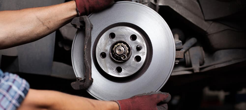 Car Mechanic repairing brakes