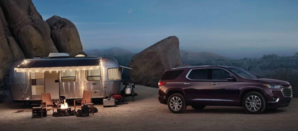 Chevy Traverse and camper it towed parked for a night of camping