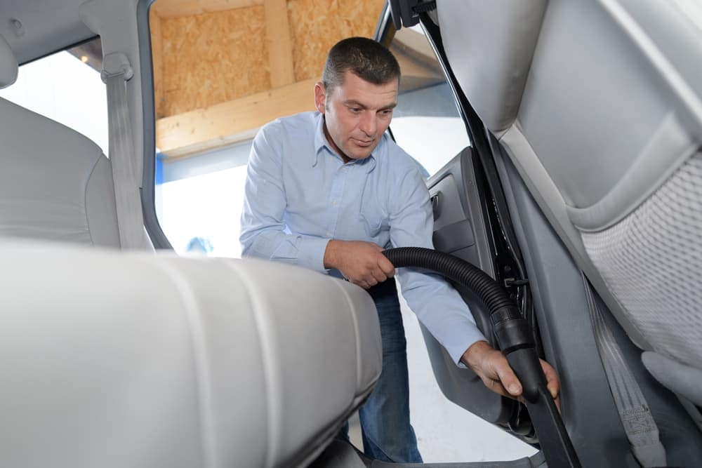 Man vaccuming floor mats