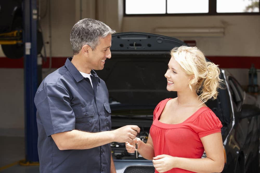 Woman receiving car keys from mechanic after service