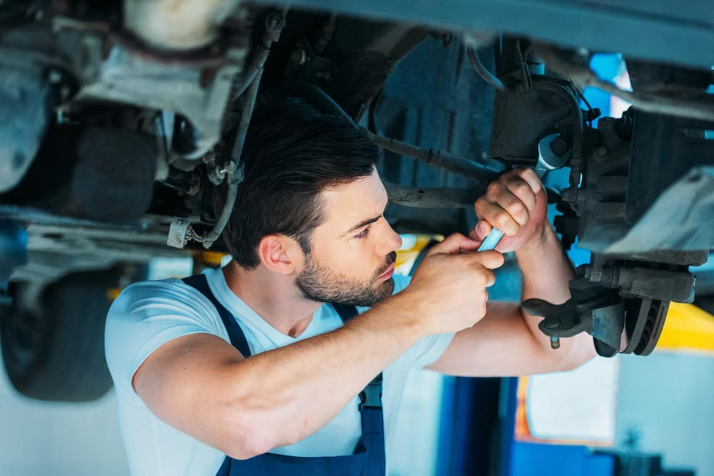Auto mechanic performing work under car