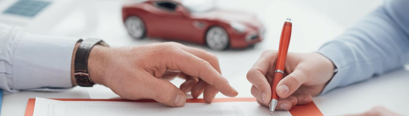 Financing paperwork with a model car in the background