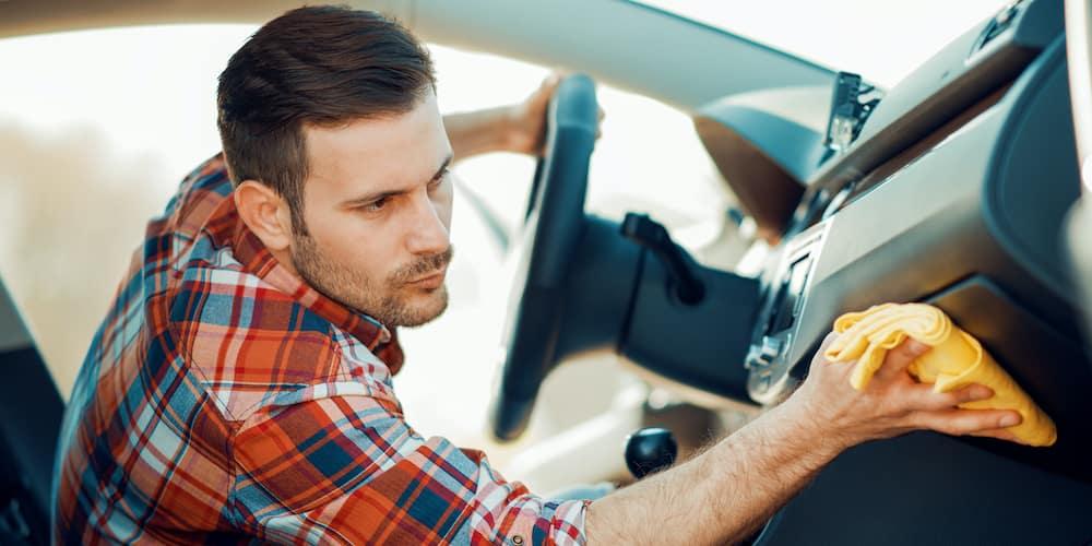 Man cleaning a car dashboard